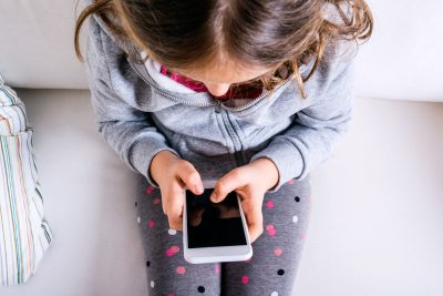 60991453 - little girl sitting on sofa with a smart phone. happy child playing indoors.